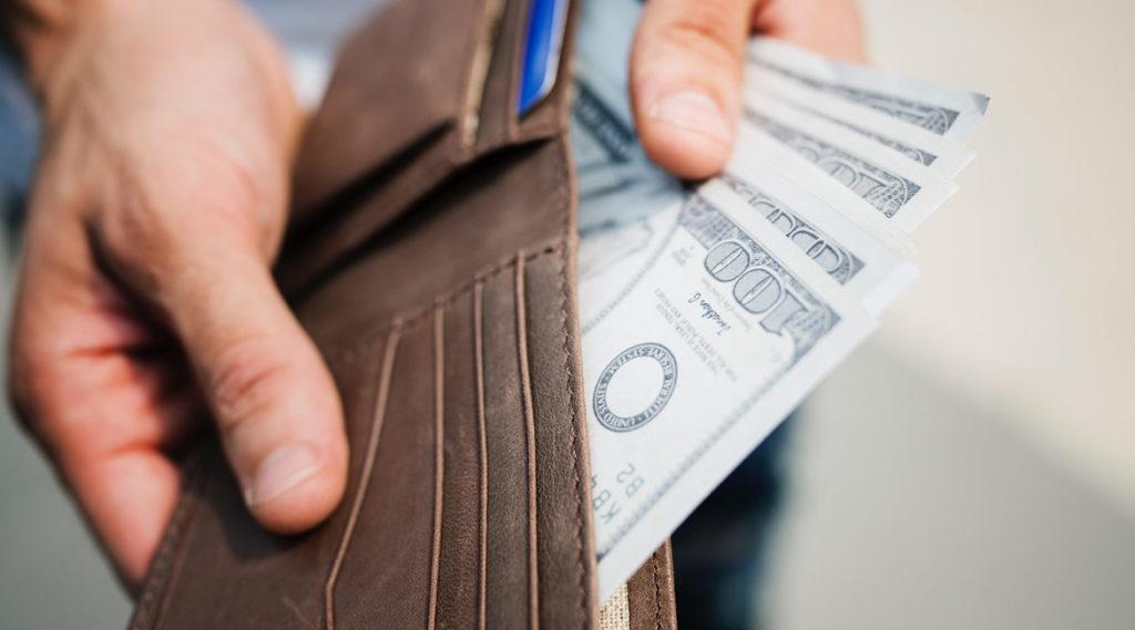 Mężczyzna sprawdza w portfelu czy starczy mu gotówki na zakupu