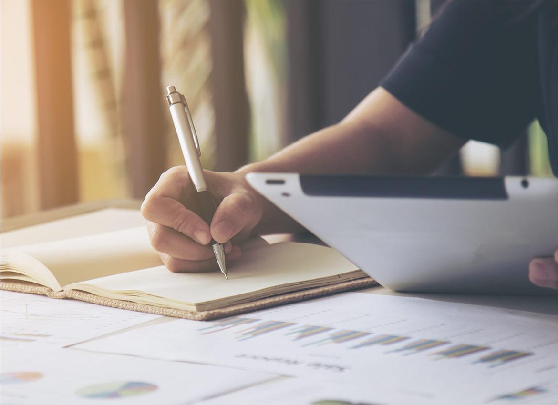 Inwestor zapisujący wyniki inwestycji w notesie