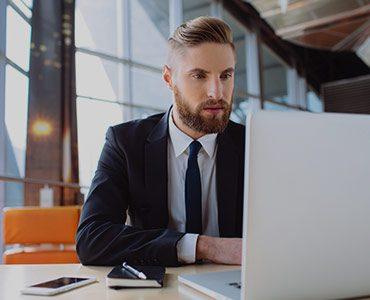 Elegancki inwestor z uwagą obserwuje na ekranie laptopa wyniki inwestycji