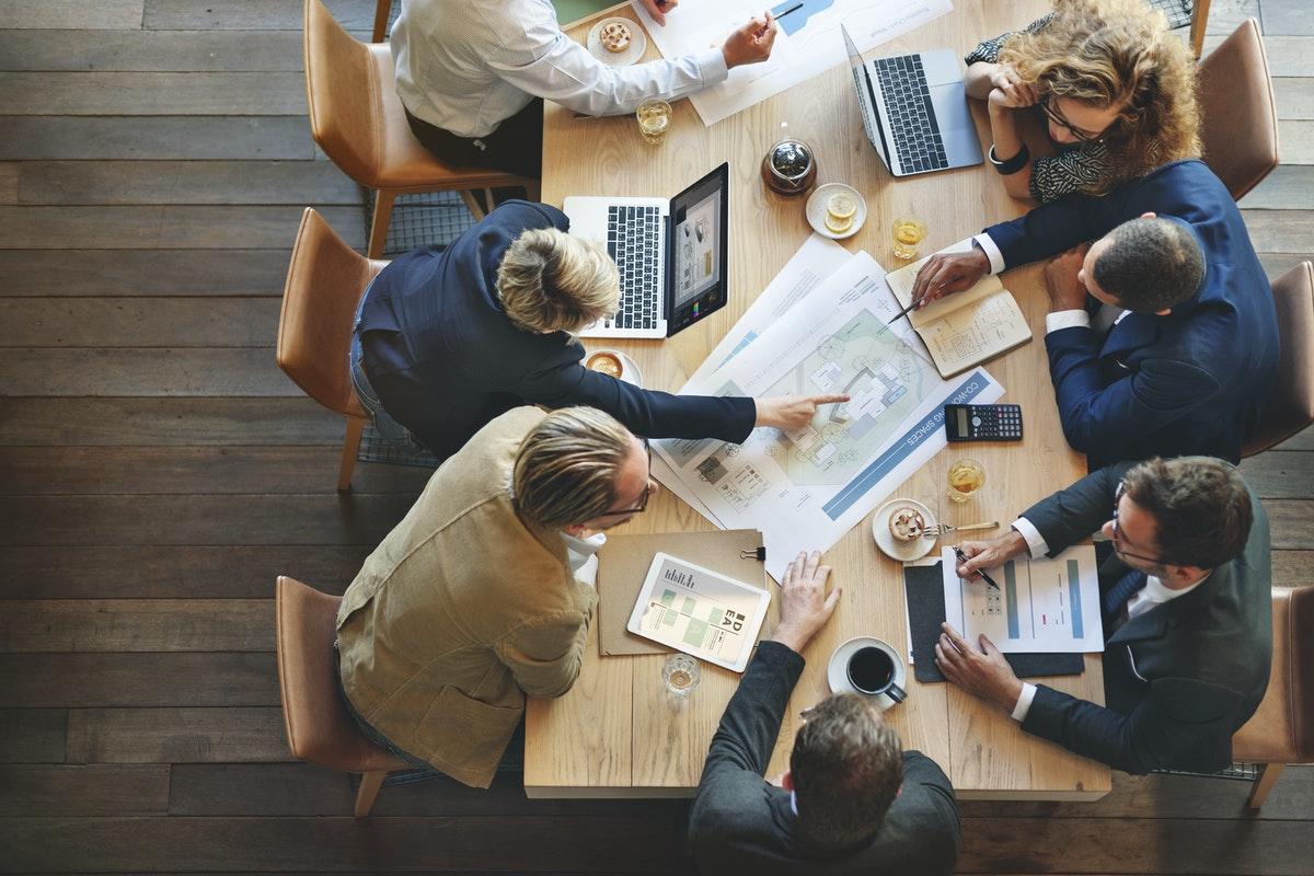 Grupa przedsiębiorców i managerów omawiająca plany rozwoju firmy
