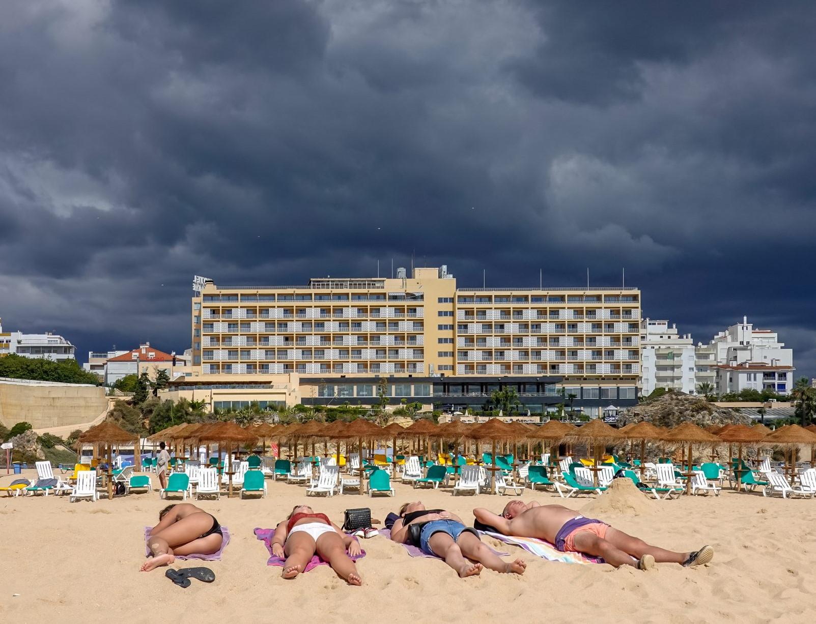 czworo plażowiczów leżących beztrosko, nieświadmomych nadciągającej apokalipsy