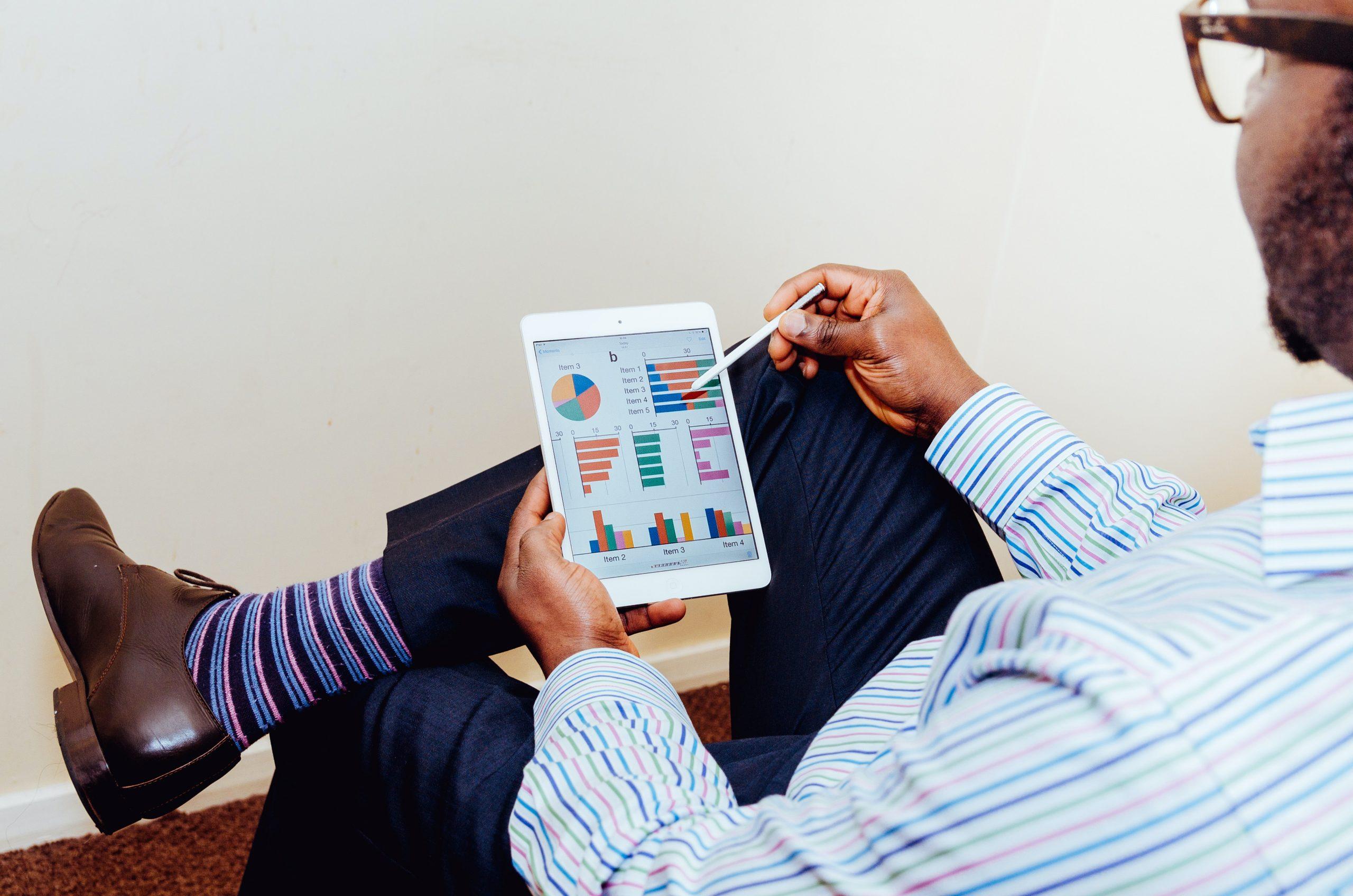 Mężczyzna analizuje dane za pomocą aplikacji umieszczonej na tablecie