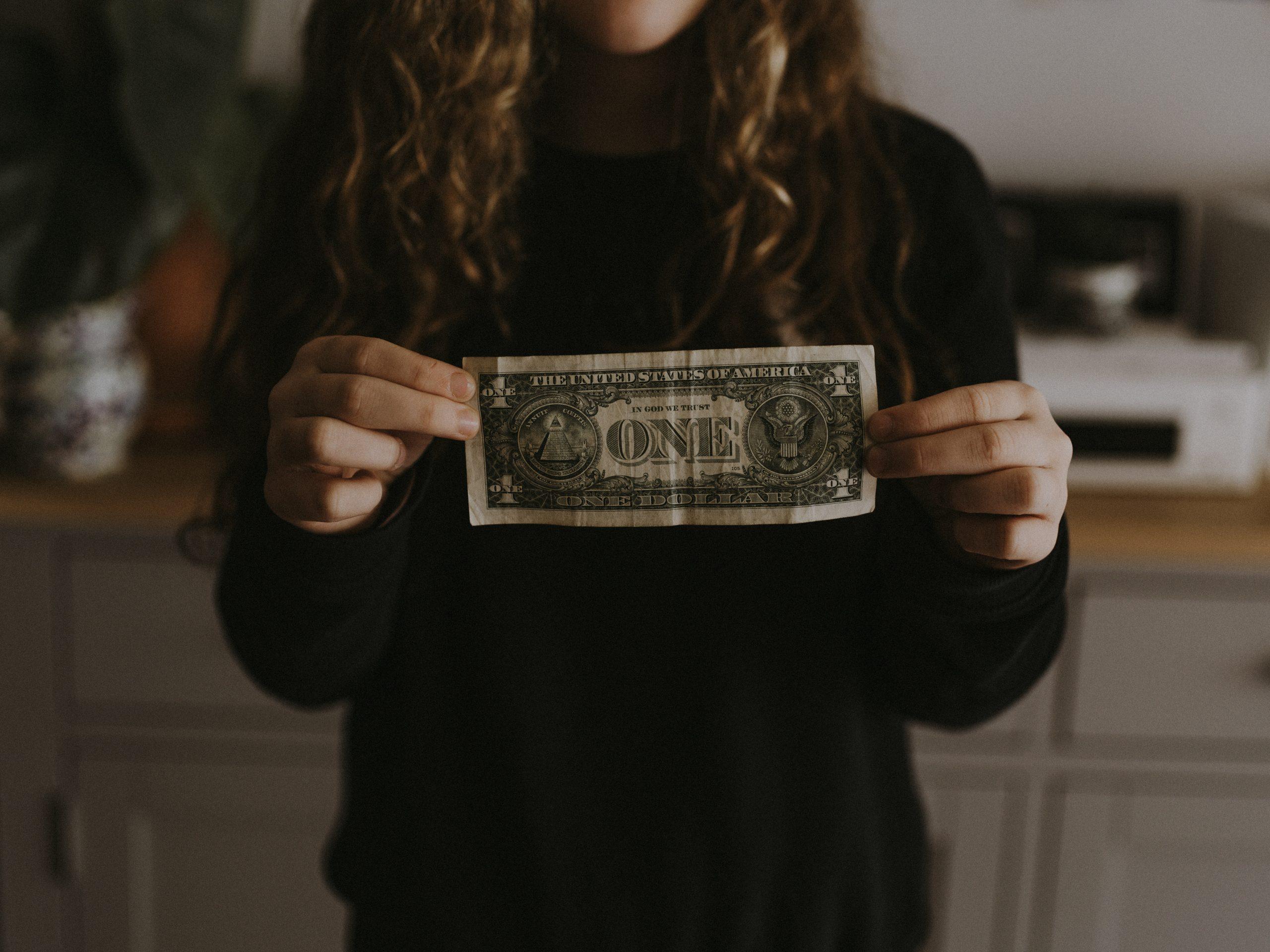Kobieta trzymająca banknot jednodolarowy