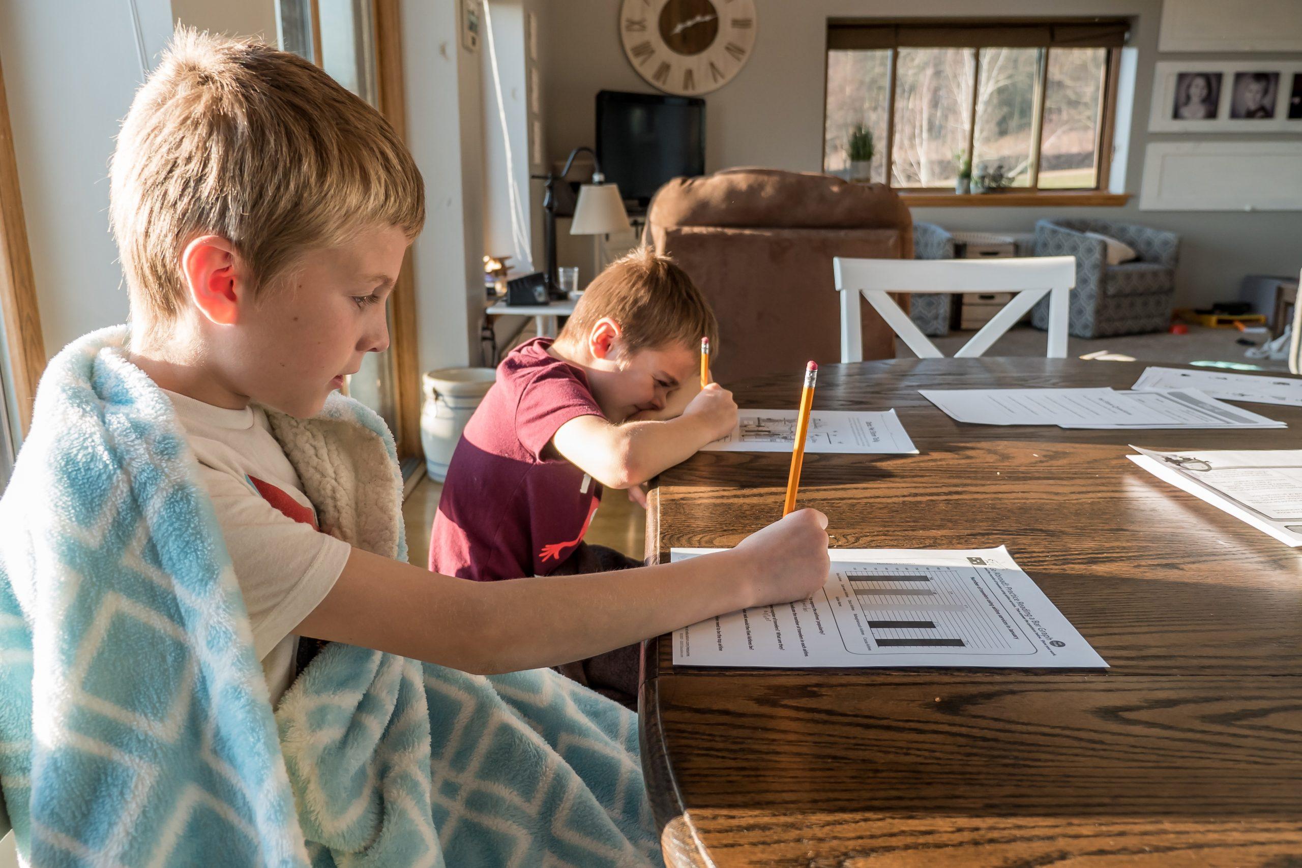 dwójka dzieci rowiązuje testy szkolne